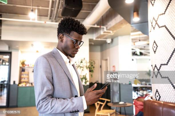 young businessman using mobile phone at coworking - businesswear stock pictures, royalty-free photos & images