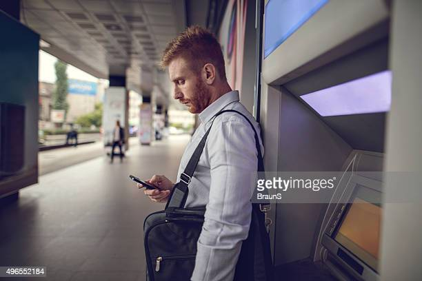 young businessman using mobile phone next to a cash machine. - ginger banks stock pictures, royalty-free photos & images