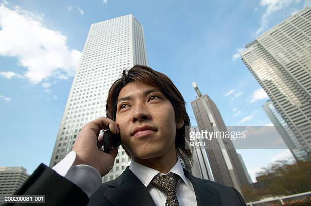Young businessman using mobile phone, skyscrapers in background, low angle view