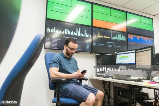 クリエイティブ ・ オフィスの大画面テレビで座りながら携帯電話を使用して青年実業家 - 大型テレビ ストックフォトと画像