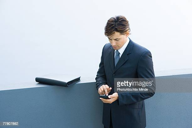 Young businessman using palmtop, looking down, high angle view