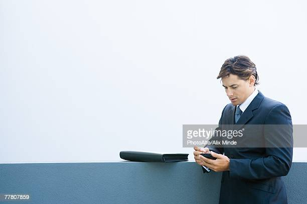 Young businessman using palmtop, looking down