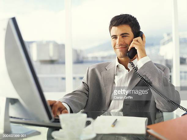 Young businessman using PC and phone