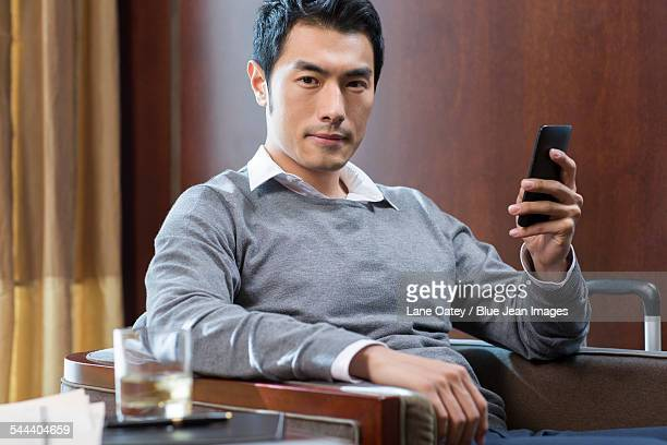 Young businessman using smart phone in hotel room