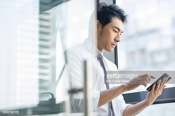 Young businessman using smart phone in office