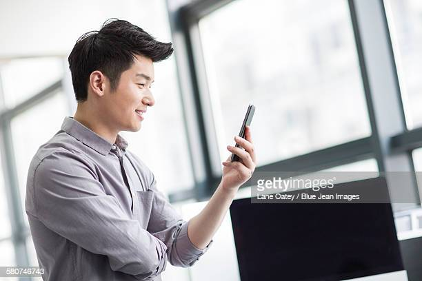 young businessman using smart phone in office - 外れる ストックフォトと画像