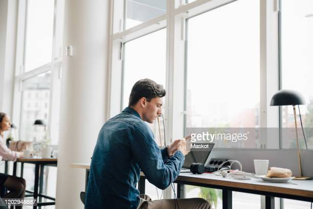 young businessman using smart phone while sitting with laptop at desk in office - incidental people stock pictures, royalty-free photos & images