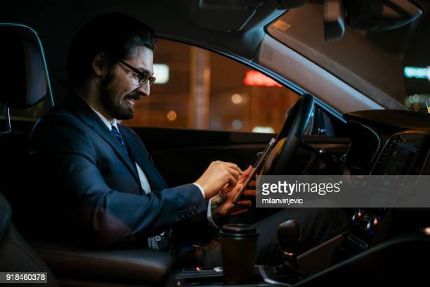 Young businessman using smartphone while driving