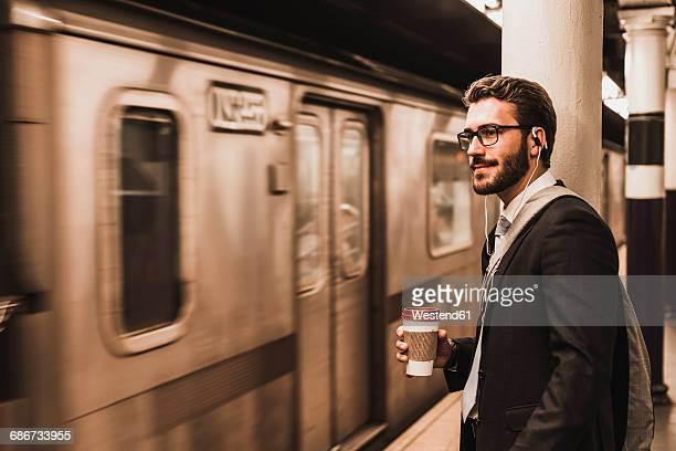 young businessman waiting at metro station platform, holding disposable cup - passageiro diário - fotografias e filmes do acervo