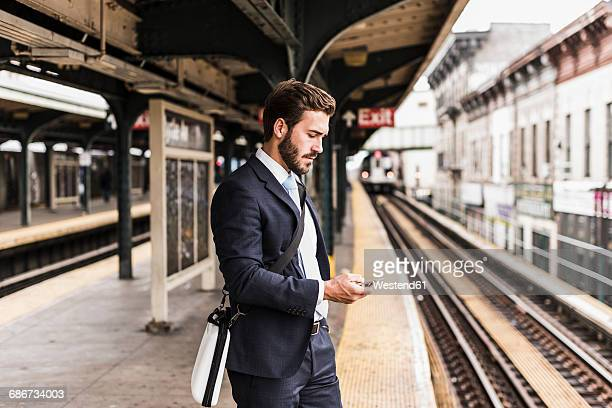 young businessman waiting at metro station platform, using smart phone - subway platform stock pictures, royalty-free photos & images