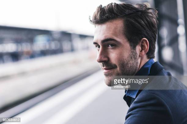 young businessman waiting at station platform - bahnhof stock-fotos und bilder