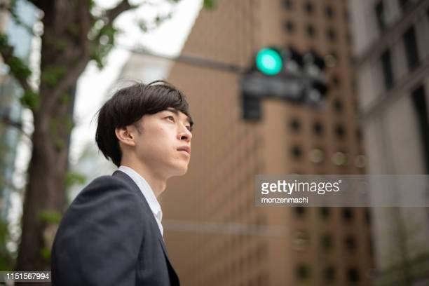交通信号を待っている若いビジネスマン - 20代 ストックフォトと画像