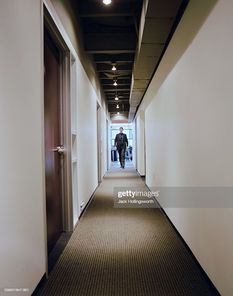 office hallway. Young Businessman Walking Down Office Hallway : Stock Photo