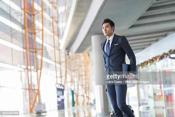 Young businessman walking in airport with suitcase and laptop