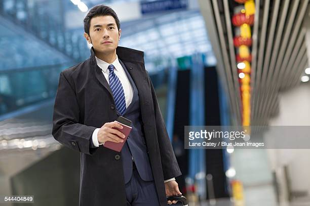Young businessman walking in airport with suitcase and passport