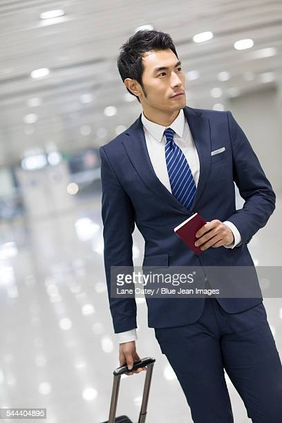 Young businessman walking in airport with suitcase