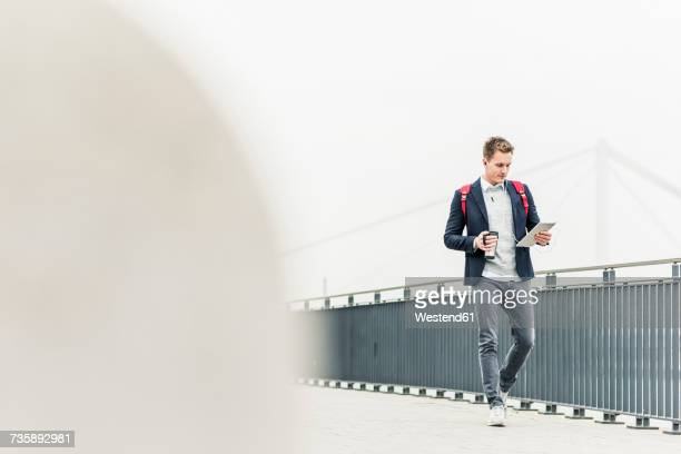 Young businessman walking in the street, carrying digital tablet and ear phones