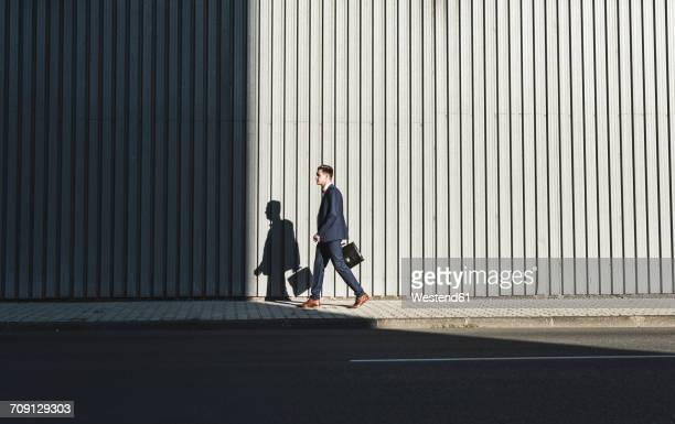 Young businessman walking on pavement