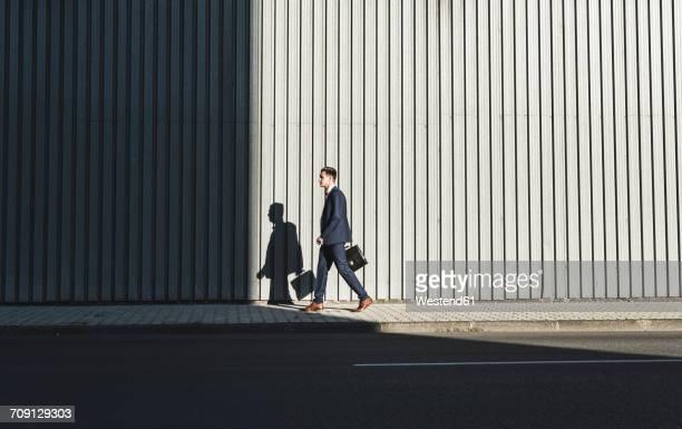young businessman walking on pavement - schlagschatten stock-fotos und bilder