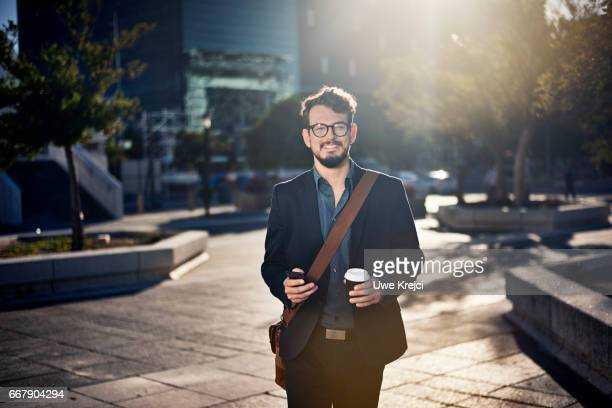 Young businessman walking on sidewalk holding smart phone and coffee cup
