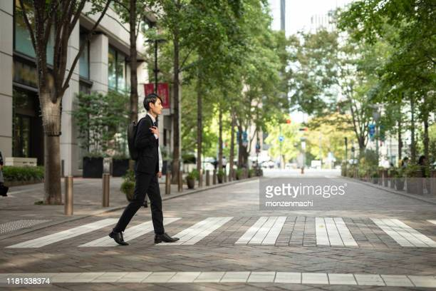 シマウマの交差点を歩く若いビジネスマン - 丸の内 ストックフォトと画像