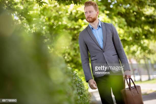 Junger Geschäftsmann zu Fuß durch den Stadtpark