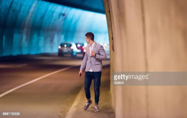 Young businessman walking trough the tunnel.