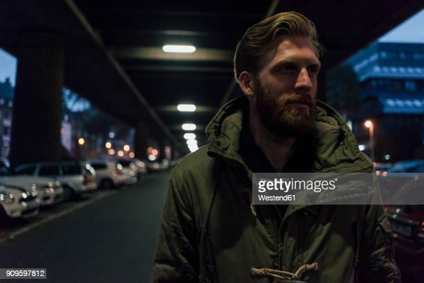 young businessman walking under bridge at nicht - ein mann allein stock-fotos und bilder