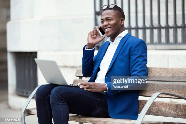 young businessman wearing blue suit jacket sitting on bench and using smartphone - giacca da abito foto e immagini stock