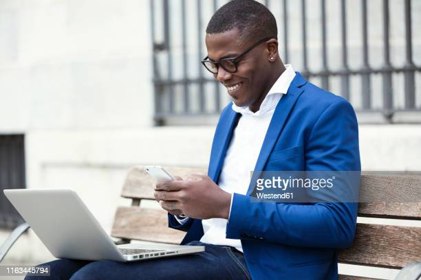 young businessman wearing blue suit jacket sitting on bench and using smartphone - blue suit stock pictures, royalty-free photos & images