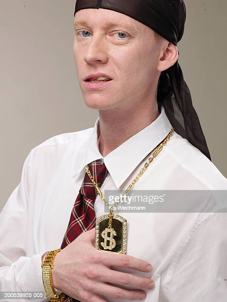 young businessman wearing do-rag and us $ sign necklace, sneering - ドゥーラグ ストックフォトと画像