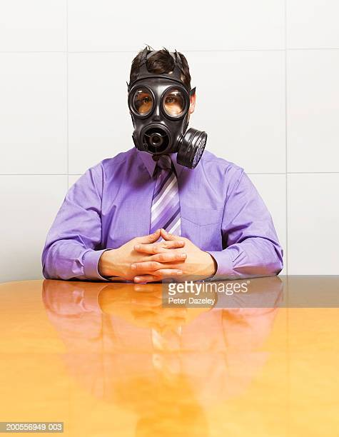 Young businessman wearing gas mask, sitting at table, portrait