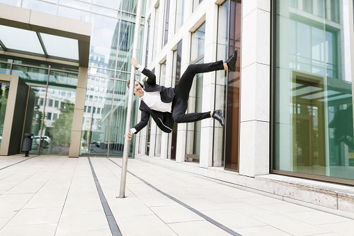 Young businessman wearing headphones jumping at lamp post in the city - gettyimageskorea