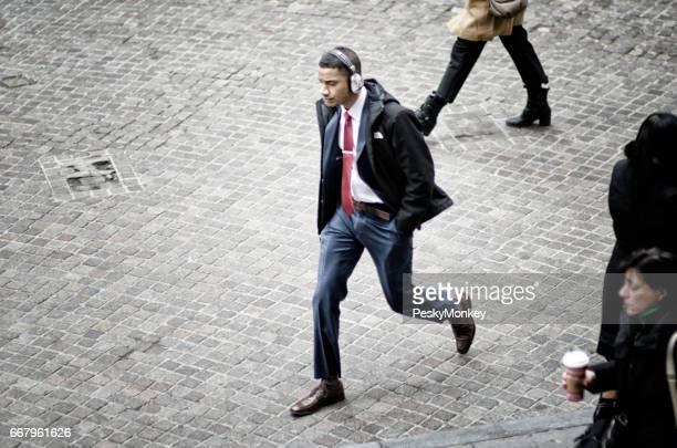 ニューヨーク シティ - 2016 年 12 月 6 日: 青年実業家は、ウォール街でその他の歩行者とヘッドフォン歩く身に着けています。