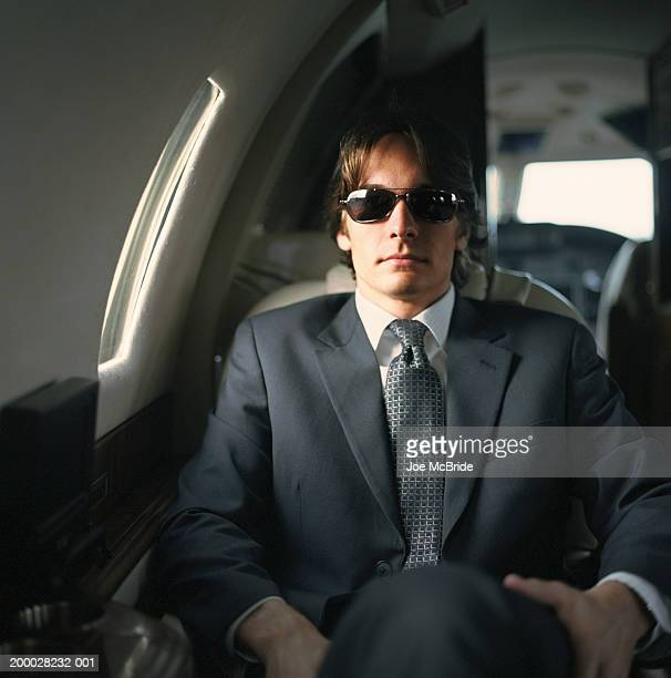 Young businessman wearing sunglasses, sitting in corporate jet