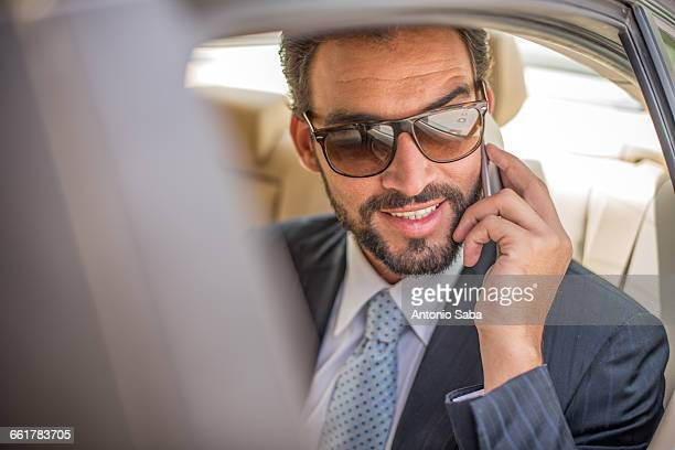 Young businessman wearing sunglasses talking on smartphone in car backseat, Dubai, United Arab Emirates