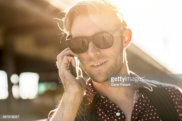 Young businessman wearing sunglasses talking on smartphone on city street