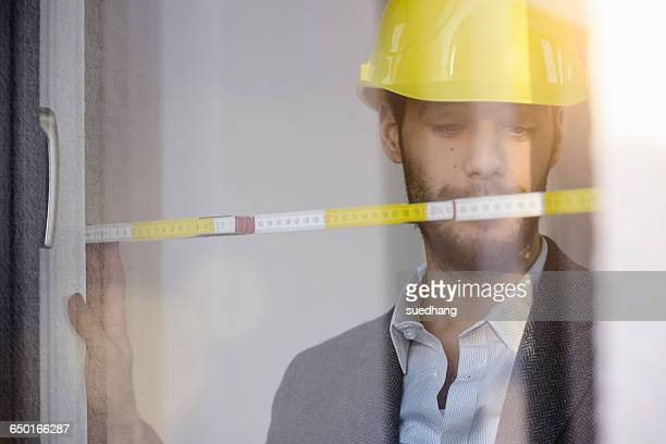 Young businessman wearing yellow hard hat measuring window in new office