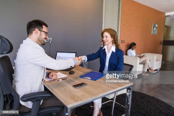 Jonge zakenman verwelkomt een nieuwe medewerker met een handdruk.