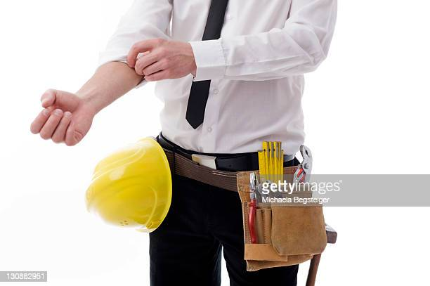 Young businessman with a tool belt and a hard hat, rolling up his sleeve