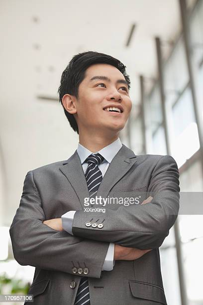 Young businessman with arms crossed smiling, portrait