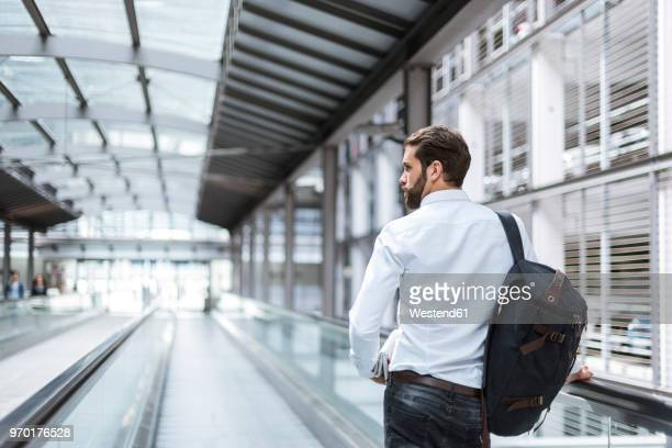 young businessman with backpack on moving walkway - weißes hemd stock-fotos und bilder