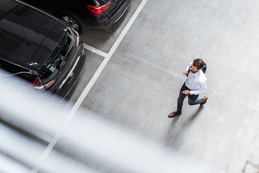 Young businessman with backpack on the go at parking garage - gettyimageskorea