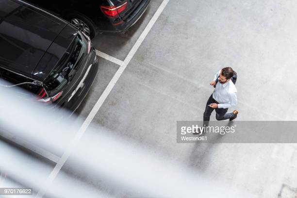 young businessman with backpack on the go at parking garage - eine person stock-fotos und bilder