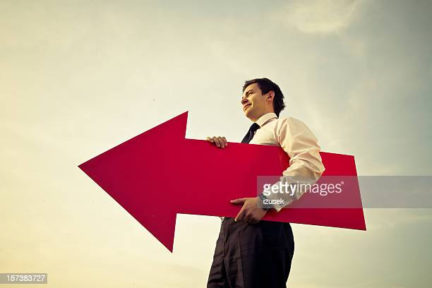 Young businessman with big red arrow