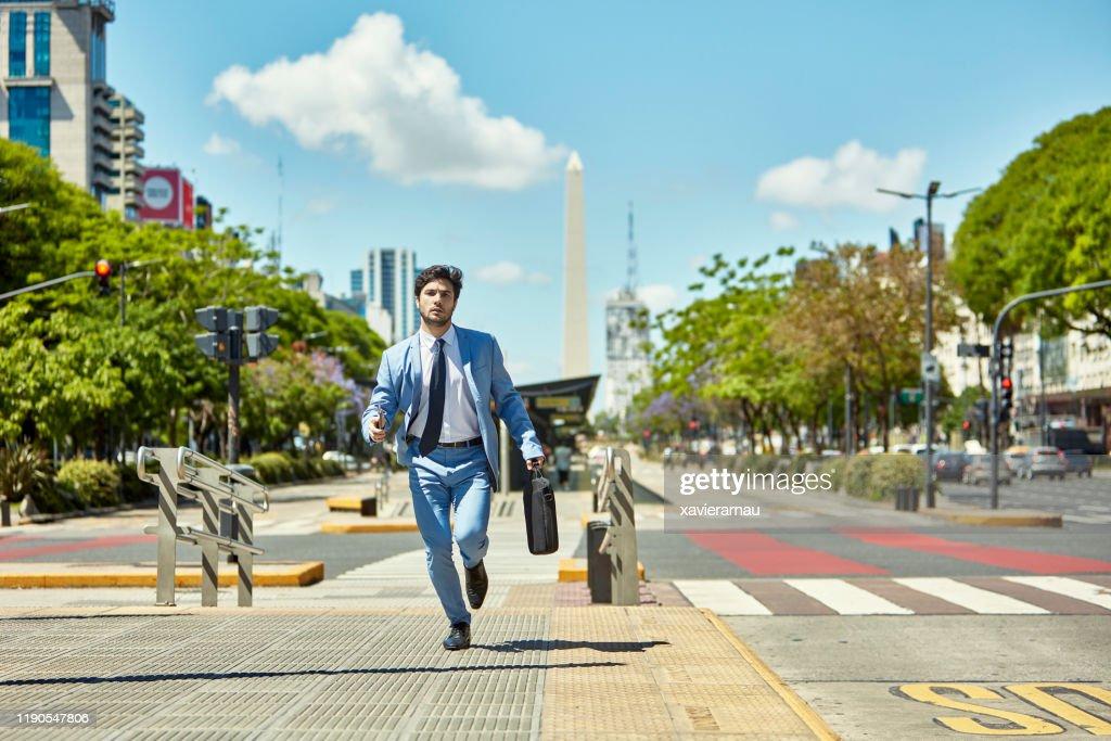 ブリーフケースを持つ若いビジネスマンが任命に走る : ストックフォト