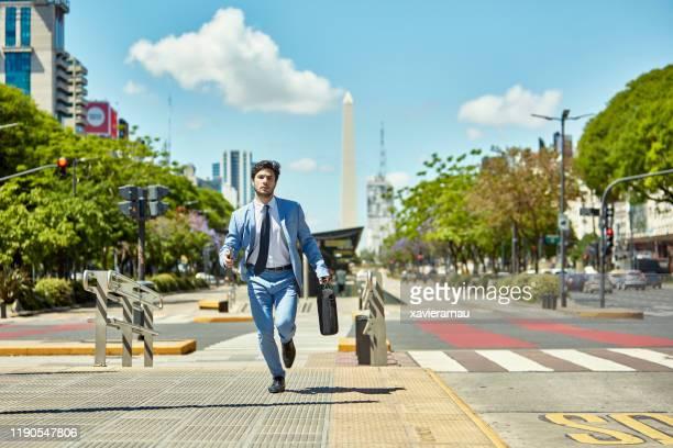 ブリーフケースを持つ若いビジネスマンが任命に走る - 接近する ストックフォトと画像