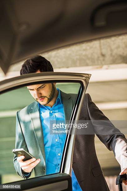 Young businessman with cell phone getting into car