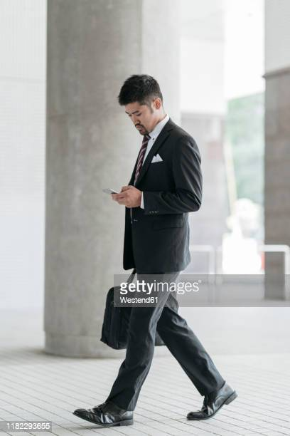young businessman with cell phone walking in the city - pedestrian stock pictures, royalty-free photos & images