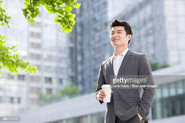 young businessman with coffee cup - オープンネック ストックフォトと画像